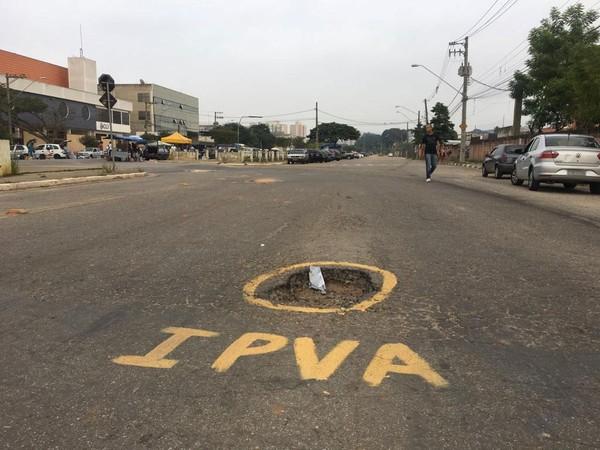 Buracos em ruas e avenidas são pintados com as siglas 'IPVA' e 'IPTU'